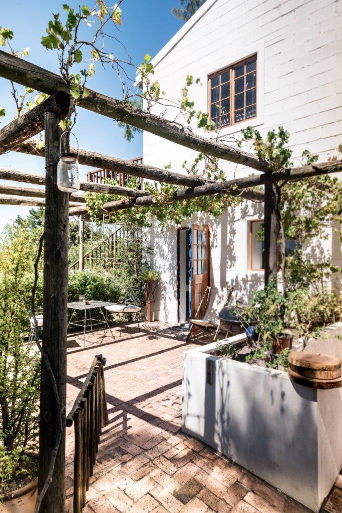 Blue Sky, White Double Storey Country Apartment with Garden Terrace Partially Covered With Creeping Grape Vines