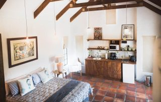 neat living room with high ceiling and exposed roof trusses and kitchen and double bed