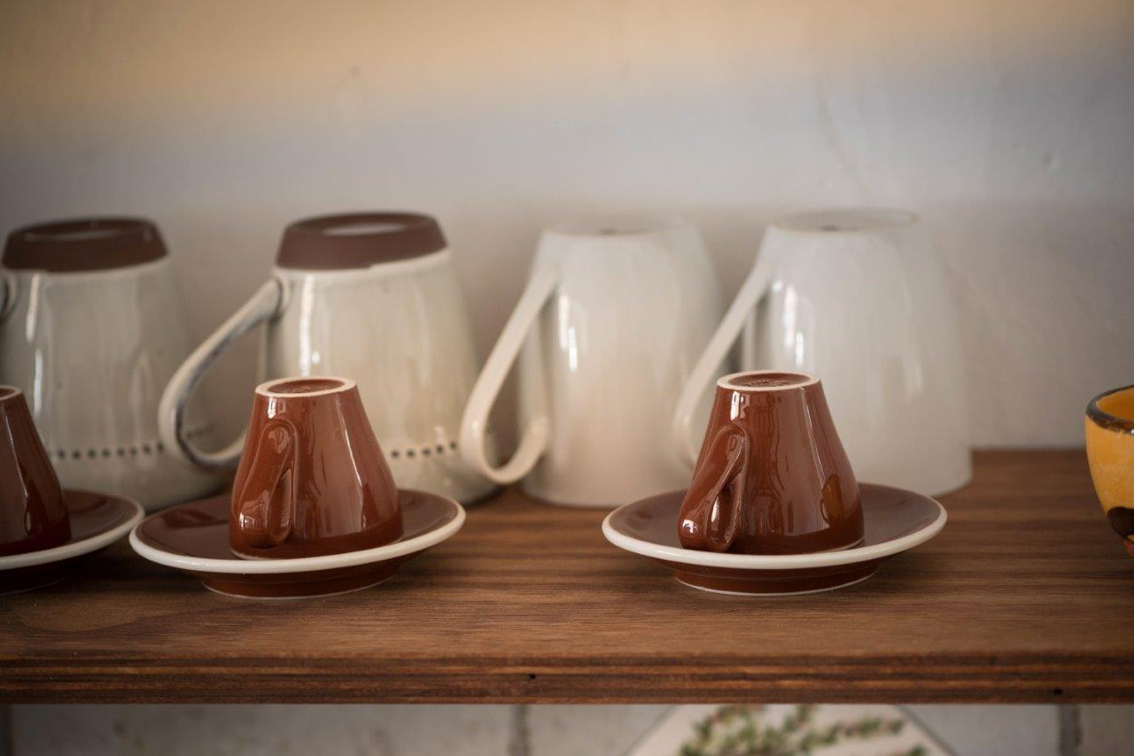 brown Upside-down cup over saucer on shelf