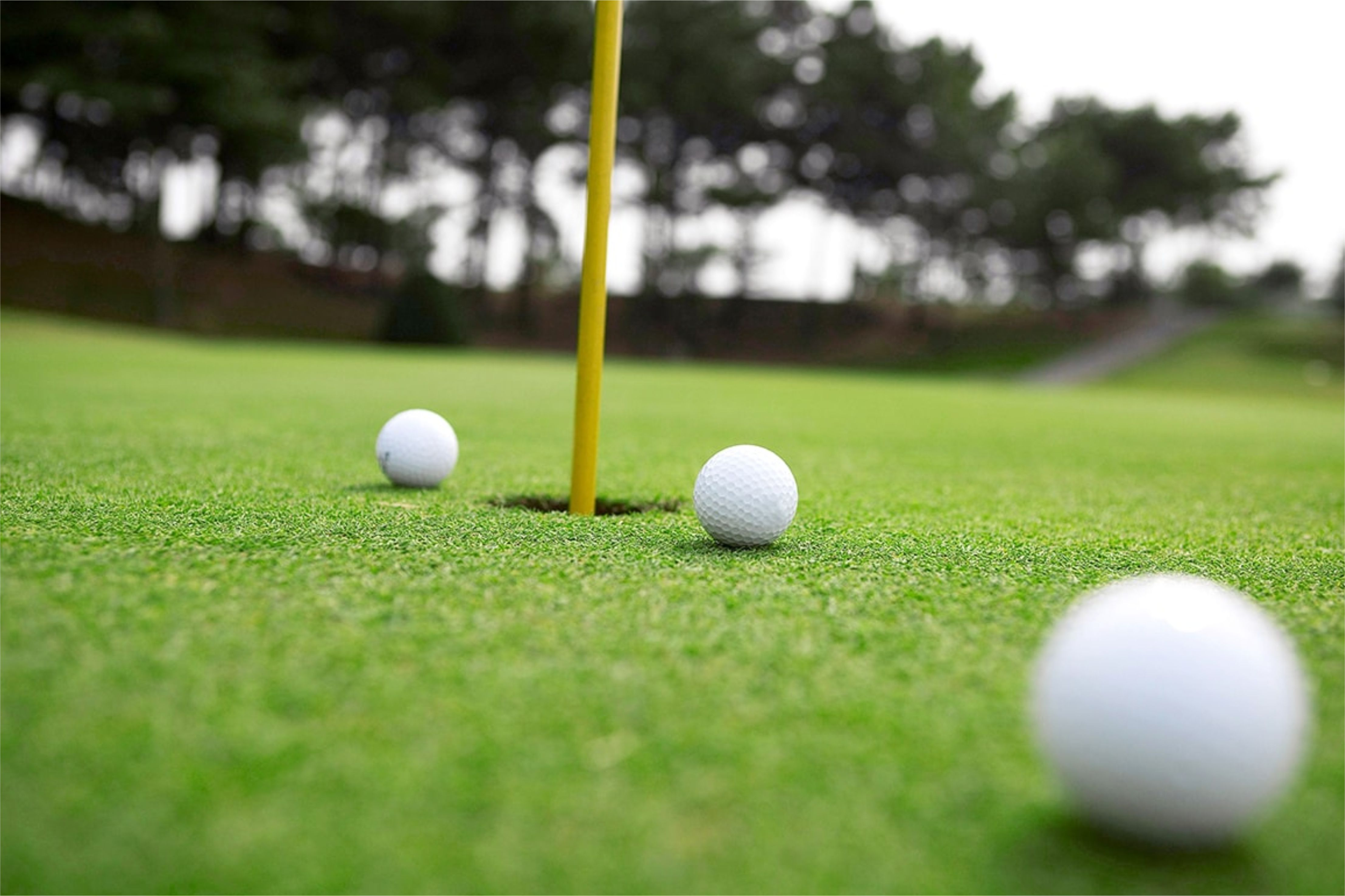3 golf balls round about flag hole golf meadow grass lawn